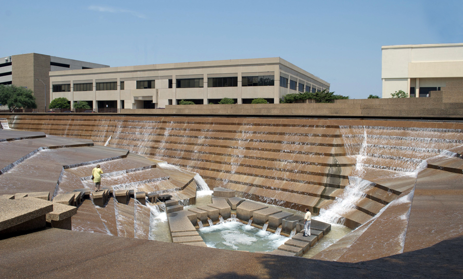 """Fort Worth Water Gardens, 1974, Philip Johnson & John Burgee, 1502 Commerce St., Downtown. The """"Active Pool"""" is the dramatic focal point of the Water Gardens, with a 38-foot drop into a small pool at the bottom. The Gardens, a gift to the city from the Amon Carter Foundation, were used as a location in the 1975 feature film """"Logan's Run"""" and in the TV adaptation of """"The Lathe of Heaven"""" in 1979."""