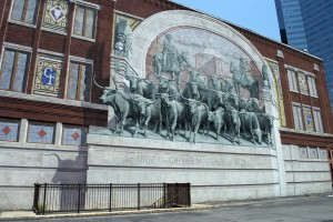 """""""Chisholm Trail Cattle Drive"""", 1988, Richard Haas, 400 Main St., Downtown. The trompe l'oeil painting of a longhorn stampede on the side of the 1902 Jett Building commemorates the 19th century Chisholm Trail cattle drives that were crucial to the growth of Fort Worth. The three stories-tall painting by Richard Haas includes the dates """"1867-1878"""" in reference to the time period that the famous cattle drives came through town on their way to the Kansas City railhead."""