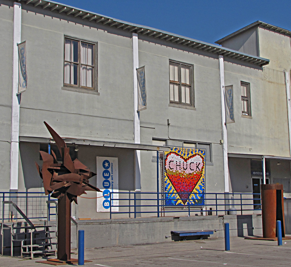 Exterior of the Blue Star Contemporary Art Center. Note tribute to artist, bon vivant and board member Chuck Ramirez (1962-2010), put together by Alex Rubio's Blue Star-funded MOSAIC high school arts program, using a technique from Gary Sweeney.