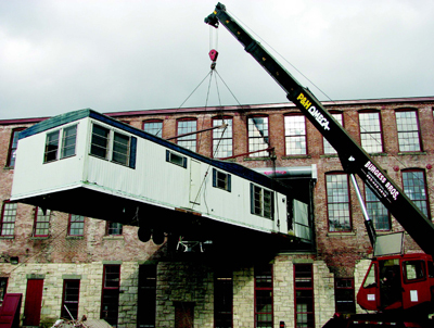 Exterior of the Massachusetts Museum of Contemporary Art during the installation of the unfinished work Training Ground for Democracy by Christoph Bchel, North Adams, 2006. Photo: John Carli. via NEWSgrist