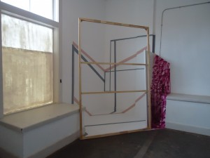 Sarah Cain, three, four, eight pm, stretcher bar, door, bells, string, spray paint, acrylic, tape, pencil on wall and floor, 2011.