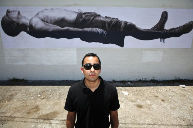 "Vincent Valdez stands in front of his piece ""Death of the Prizefighter"" outside of the Family Dollar store next to the Guadalupe Gallery. ANDREW BUCKLEY / EXPRESS-NEWS"