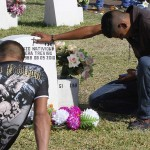 "original caption: ""Young men sit near the grave stone of a 22-year old slain in drug-related violence."""