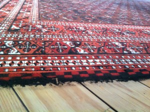 Intemperie, detail of rug slowly being blown away by the wind