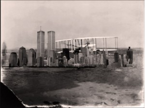 NYC attacked by giant biplane, and who's the figure peeking out over the building at right? And what kind of terrain is that/ is it water?