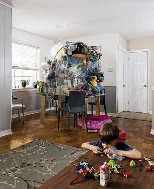 """Emmett plays with his Legos on the coffee table because the kitchen table in the background has been absorbed into an art project of stuff wrapped up into a mountain.  We began working with piles of stuff in our house with our video, """"Accumulation"""" where we created a pile of stuff in the garage and climbed up it."""