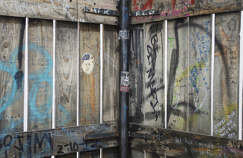 """Fence (JFK version),"" 2013, Wood, metal, ink, marker pen, tippex, tape, dirt, crayon, paper, spray paint, graphite, Long section: 168 x 59 x 6 inches, Short section: 108 x 59 x 6 inches, Image courtesy gallery website"