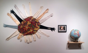"Beth Secor, You were, now are, the world of me, consists of embroidery of Alzheimer's MRI embellished with vintage kid and silk gloves (2013), photograph of Beth Secor standing, assisted by Shirley Secor, surrounded by Susan and Shirley Secor, mounted on found embroidered linen (1957), 12"" repogle globe (1976-1991)"