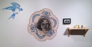 Beth Secor, This is terrible (this is sublime), Drawing of Shirley Secor in ink and White Out on vellum with embroidery, on found embroidery with beads (2013), photograph of Shirley Secor (nee Marrs) and Clara Marrs (1946), sulfur lion statue with broken head from Gulf Sulfur Company (1962); antique dog statue from Japan with hole in head (date unknown); saint statue from Mexico with head knocked off (2004)