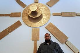 "Robert Pruitt in front of this past summer's group exhibition ""Coming Through The Gap in the Mountain on an Elephant"" at TSU's University Museum. Pruitt curated the show; Hodge was a participating artist. (Photo: James Nielsen/Houston Chronicle)"