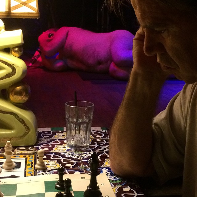 Jim Pirtle playing chess with performance art in the backgroundhellip