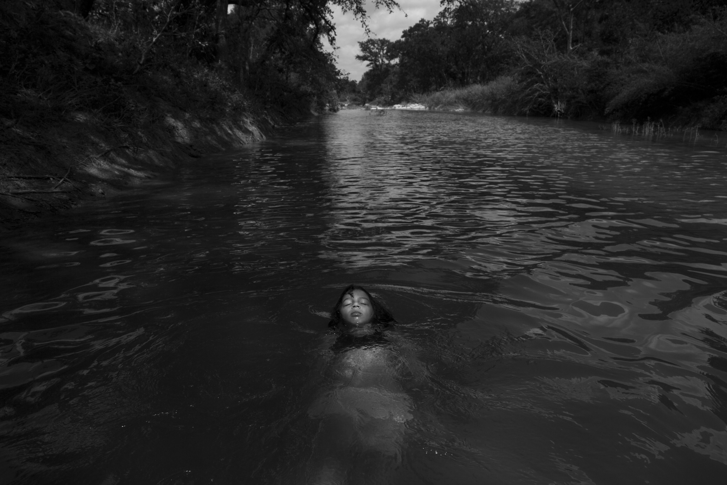 "Photo by Carolyn Van Houten. ""Serenity Bamberger floats in the Little Blanco River along their property on August 18, 2015 in Blanco, Texas. Three months prior, over Memorial Day, the same river flooded their home and business destroying the majority of the family's belongings and source of income. The Memorial Day weekend flooding, which affected Texas and Oklahoma, killed 24 people according to The Associated Press."""