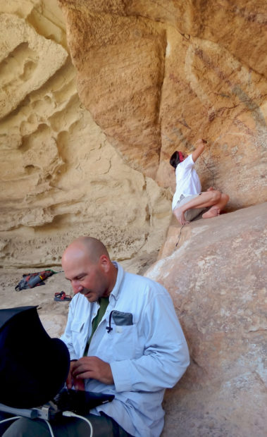 Archaeologists working with a digital field microscope. With the microscope placed at the analysis location, the microscope is connected via USB to a laptop where the microscopic imagery is viewed and photographs are captured.