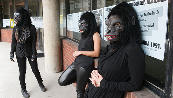 The-Guerrilla-Girls-standing-in-front-of-their-posters