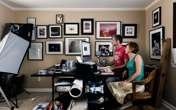 """We use our entire house as a studio: to shoot videos and photographs in, to construct sculptural installations in and to edit and manage our art practice.  Here we are sitting at the work computer amidst the lights and other equipment. Behind us is a photograph from the House/hold series of our dog, Penny, titled """"Cerebus."""""""