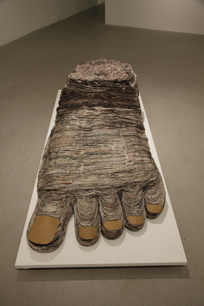 Barefoot and Pregnant, 2013, cut and stacked newsprint, cardboard, glue, 18 x 36 x 72 inches