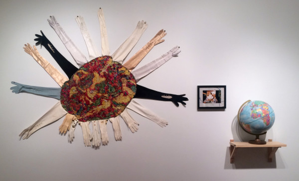 """Beth Secor, You were, now are, the world of me, consists of embroidery of Alzheimer's MRI embellished with vintage kid and silk gloves (2013), photograph of Beth Secor standing, assisted by Shirley Secor, surrounded by Susan and Shirley Secor, mounted on found embroidered linen (1957), 12"""" repogle globe (1976-1991)"""