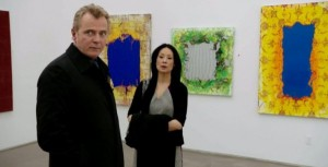Actors Aidan Quinn and Lucy Liu in front of Mark Flood paintings. (Courtesy CBS)