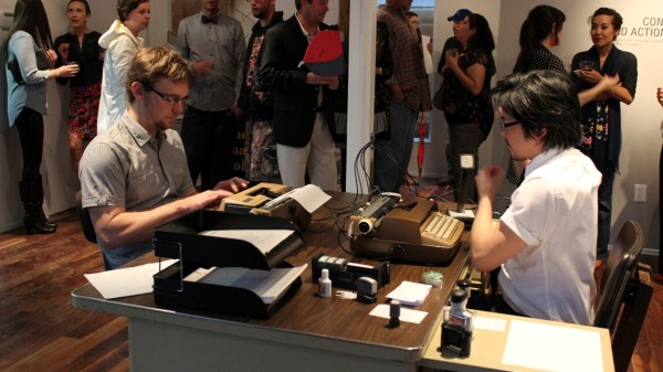No Talking, Just Typing, 2010 (ongoing). Performance with two typewriters, microphone, electronics, office supplies; performed in San Antonio, Houston, and Honolulu; photo from 2014 performance at The Mariago Collective, Houston.