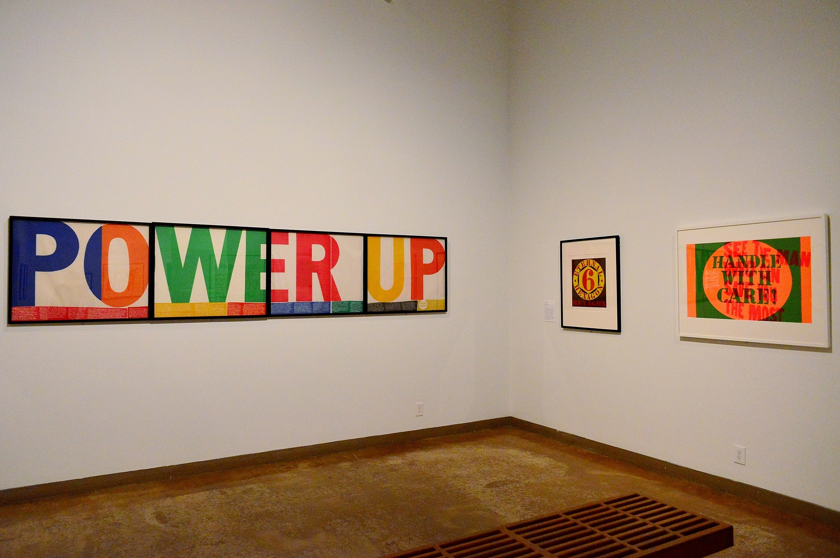 External Hexagon by Robert Indiana (c) flanked by two Corita Kent works power up (r) and handle with care (l).
