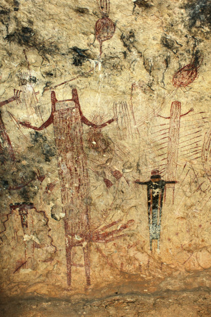 A 10-foot-tall anthropomorph in Panther Cave with upraised arms, U-shaped head, and a feather hip-cluster-like adornment on its left side. An atlatl loaded with a dart is portrayed in the figure's right hand, and in its left hand are additional darts as well as other paraphernalia.
