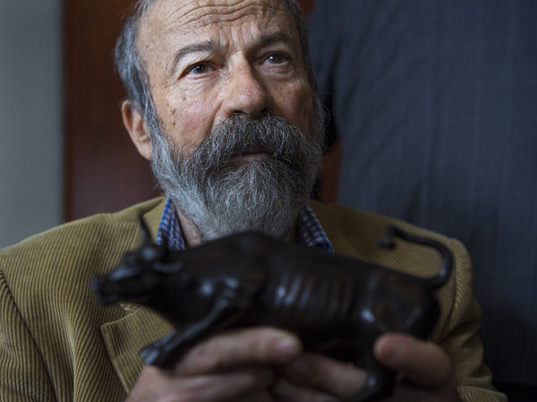 Arturo Di Modica holds a model of his Charging Bull during a news conference Wednesday.