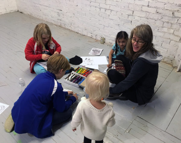 Kathryn Kelley playing drawing games with the local kids
