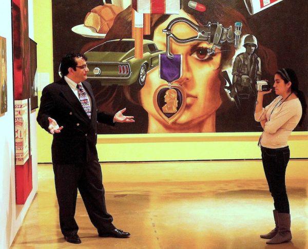 Educadora Mia Lopez graba video de Ruben C. Cordova en la retrospectiva de Treviño en el Museo Alameda en 2010. De derecha a izquierda: Mi vida (1971-72), Alamo Exit (1969), Zapata (1969), Armando Albarran (1968).