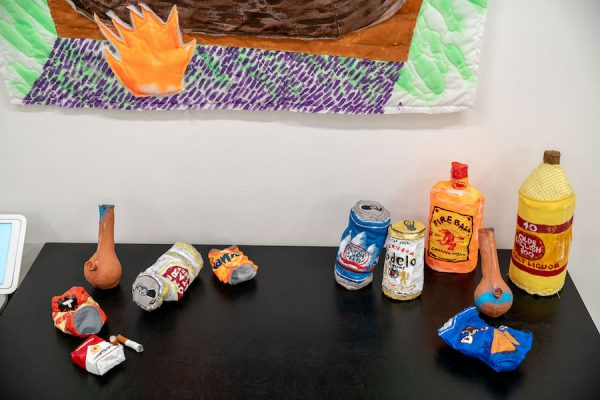 Various works by Alexis Mabry (mixed media alcohol containers, cigarettes, chips) and Steef Crombach (ceramic bongs).