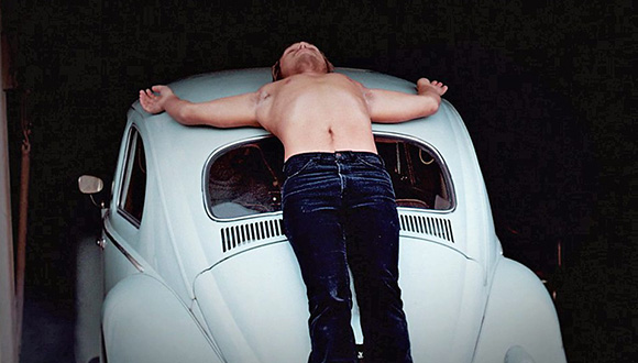 Artist Chris Burden nailed to a VW beetle