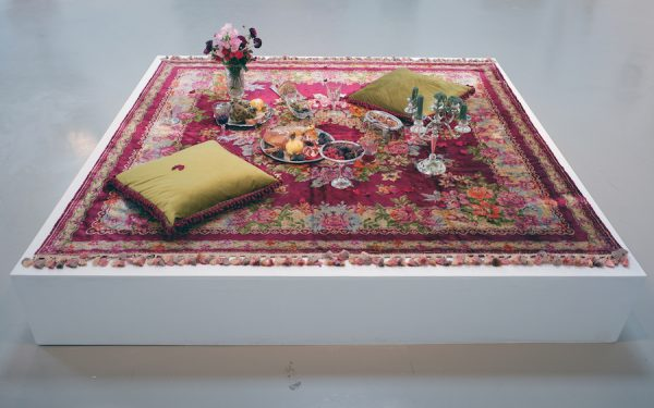 Erin Stafford, A Lover's Picnic followed by Post-Coital Tristesse, 2019. Rug, found objects, food, wine, candles. 82 x 82 x 37 inches