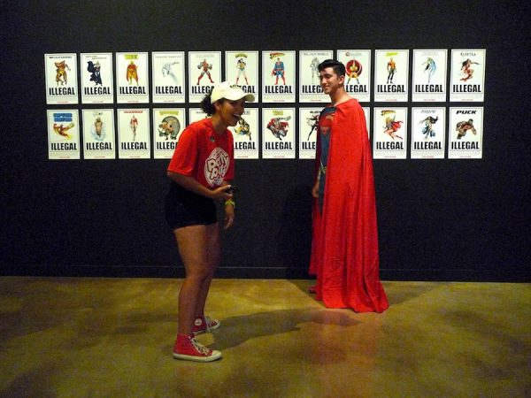 "Superman Impersonator in front of installation of 24 ""wanted posters"" in the Illegal Superheroes Series 1 (2012) by The Department of Illegal Superheroes (ICE DISH)"