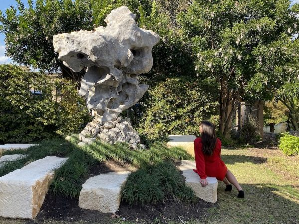 Taihu Rock contemplated by visitor, gray limestone with white veining and inclusions, 12 feet high, San Antonio Museum of Art.