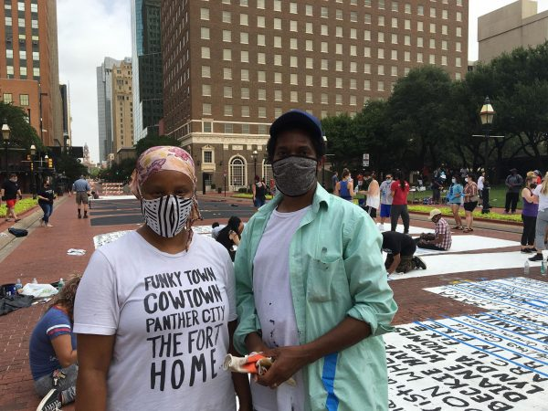 Artists Letitia Huckaby, left, and Sedrick Huckaby pose by their temporary street painting downtown Fort Worth, July 27, 2020. Photo Credit, Adam Werner
