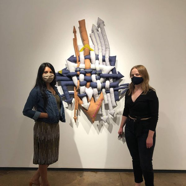 Martha Elena, left, and Evie Marie Bishop pose in front of Elena's work at Artspace 111
