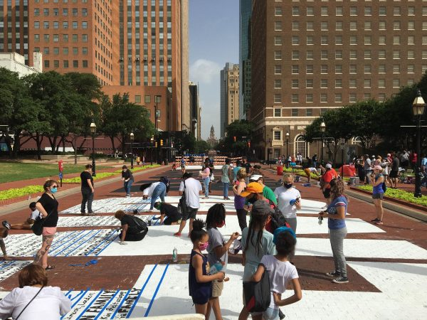 More volunteers paint their signatures onto Sedrick and Letitia Huckaby's temporary street painting downtown Fort Worth, July 27, 2020. Photo Credit, Adam Werner