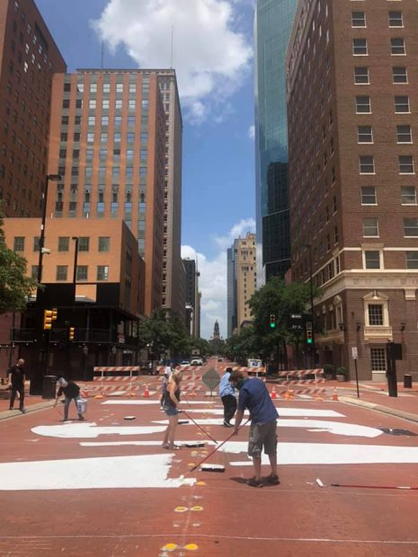 Volunteers begin painting END RACISM NOW, with the Tarrant County Courthouse in the background