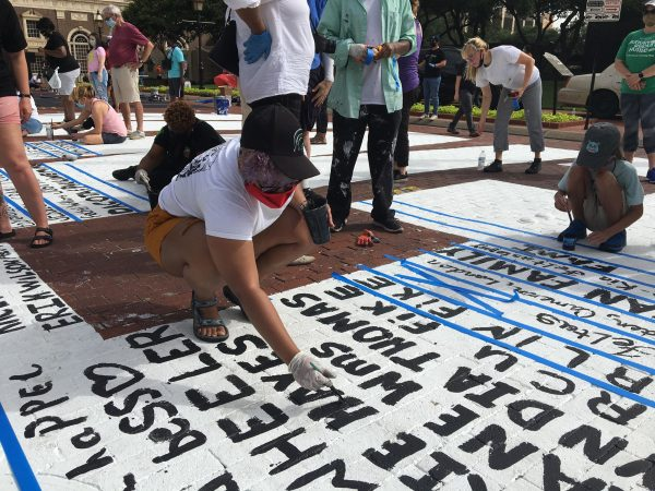 Volunteers paint their signatures onto Sedrick and Letitia Huckaby's temporary street painting downtown Fort Worth, July 27, 2020. Photo Credit, Adam Werner