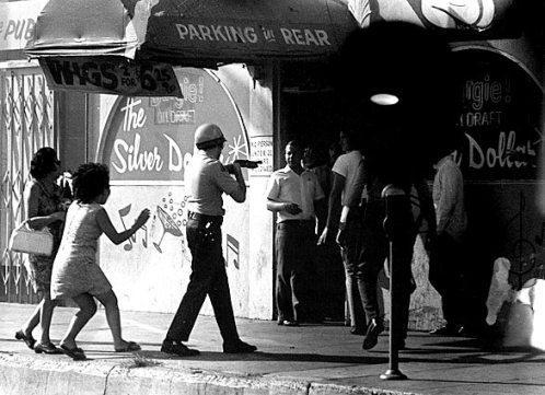 Sheriff Grasser with shotgun (or tear gas gun) forcing men into the Silver Dollar
