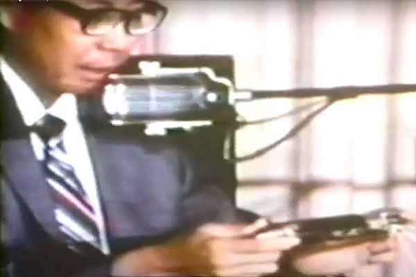 """Deputy Coroner David Katsuyama with """"Flite-Rite"""" tear gas projectile (a barricade penetrator not designed to be shot directly at people), testifying at Coroner's Inquest, 1970. Katsuyama said Salazar's head wound was consistent with the projectile."""