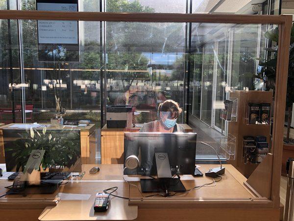 A masked employee behind a plexiglass window at the Kimbell Art Museum, July 24, 2020