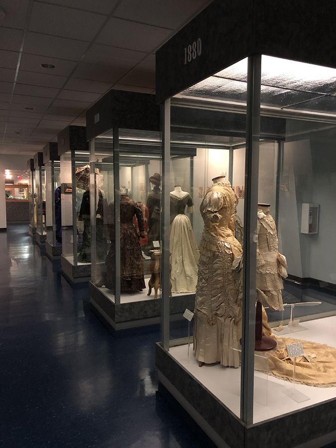 Rows of Victorian dresses from the Judy Richey's collection on display Confederat Flags on display-Texas-Civil-War-Museum-White-Settlement-TX