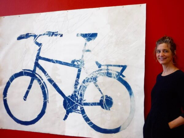 Flueckiger with one of her works in the show.