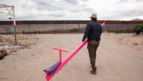 "Ronald Rael and his temporary architectural structure ""Teeter-Totter Wall"" at the U.S. Mexico Border."