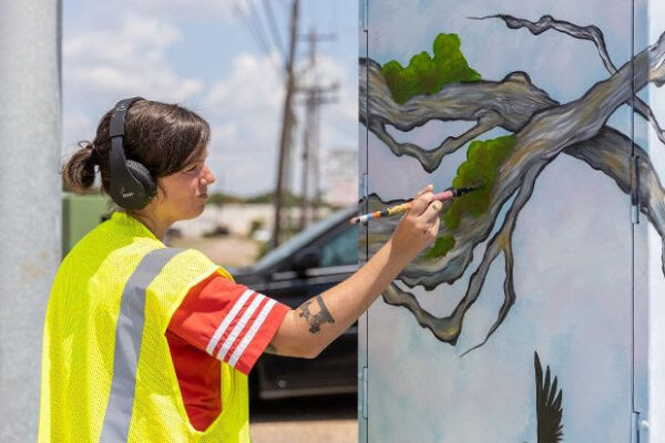 An artist commissioned by Up Art Studio paints a mini-mural on a traffic control box.