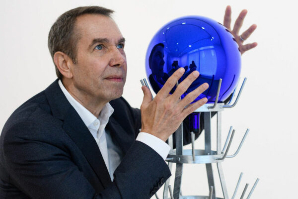 artist Jeff Koons poses with an orb artwork