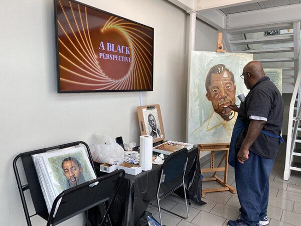 Artist Eddie Filer paints a portrait of James Baldwin at the Houston Museum of African American Culture's Juneteenth Celebration, 2021
