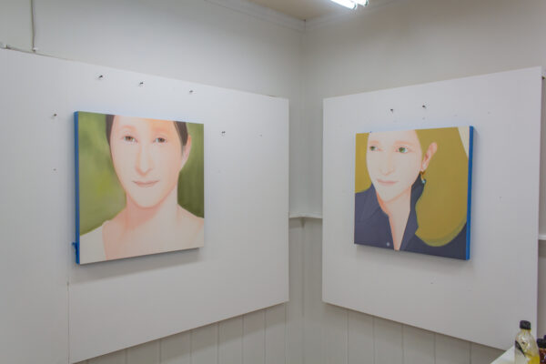 Two portrait paintings sit on either side of two walls in the studio of Wichita Falls artist Yasuyo Maruyama
